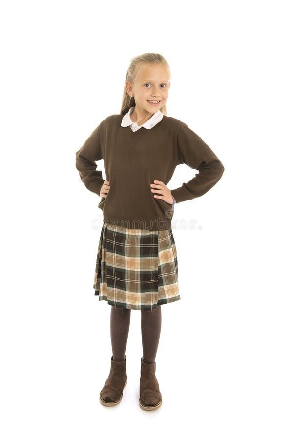 Stående av 7 eller 8 år gammalt kvinnligt barn för härlig och lycklig skolflicka i skolalikformig som ler gladlynt som isoleras p royaltyfria foton