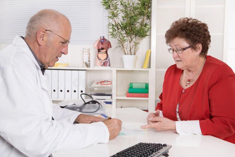 Stående av en äldre doktor som talar med hans kvinnliga patient arkivbild