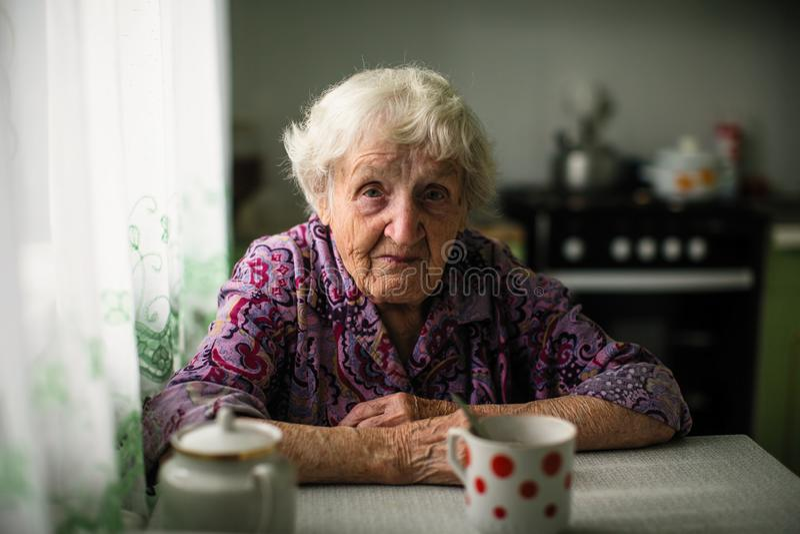 Stående av en äldre ensam kvinna som sitter på tabellen royaltyfri bild