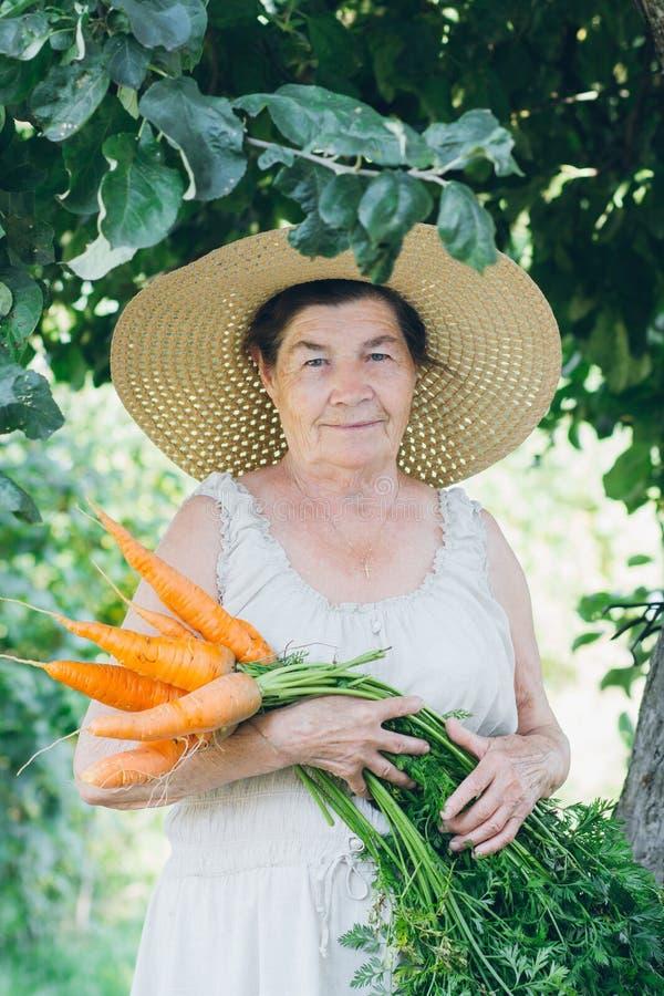 Stående av en äldre kvinna i en hatt som rymmer en morot arkivbilder