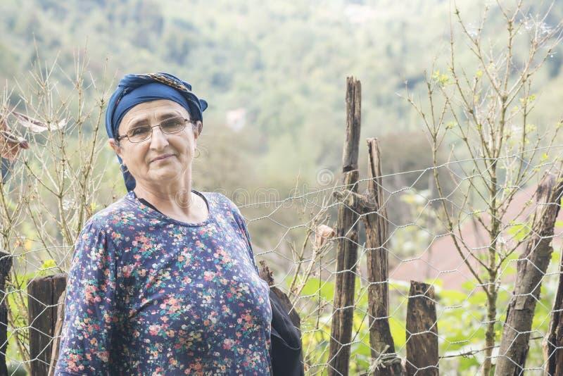 Stående av en äldre kvinna med monokeln framme av häcken royaltyfri fotografi