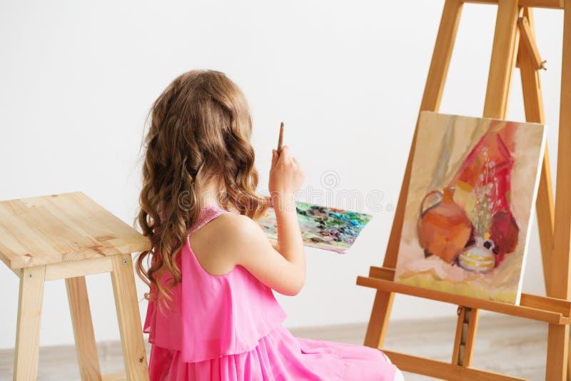 Stående av en älskvärd liten flicka som målar en bild i en studio royaltyfria foton