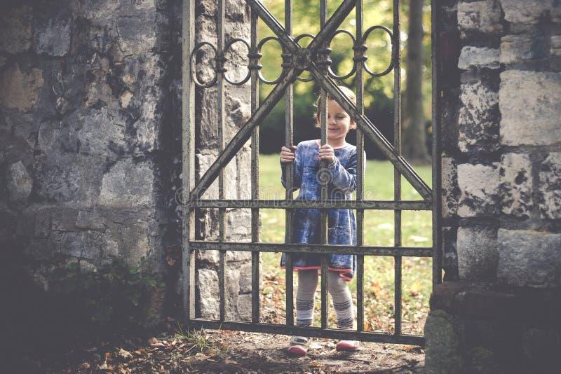 Stående av en årig flicka små fyra på en gammal järnport i en parkera i höst arkivfoton
