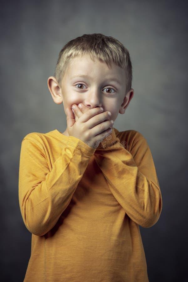 Stående av en årig pojke som 6 täcker hans mun med båda händer royaltyfri bild
