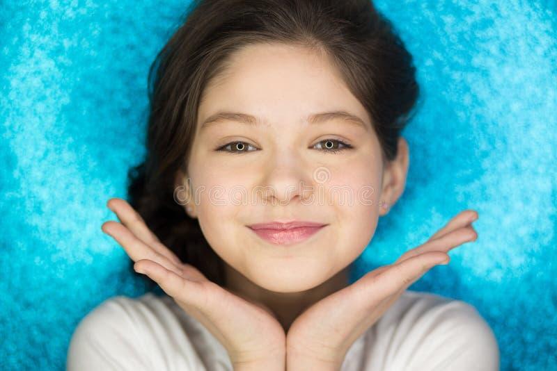 Stående av en öppen mun för lycklig upphetsad flicka som håller händer på hennes framsida som isoleras över blå bakgrund arkivbild