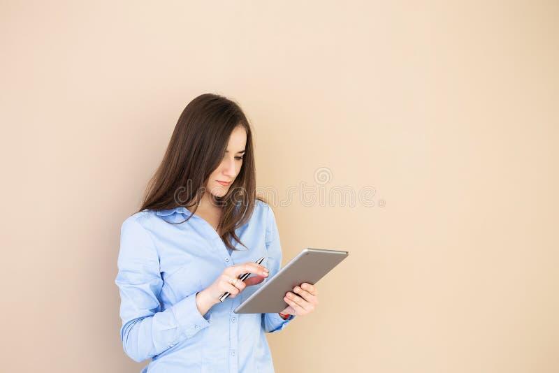 Stående av en affärskvinna som använder en minnestavla som isoleras på en beige bakgrund royaltyfri foto