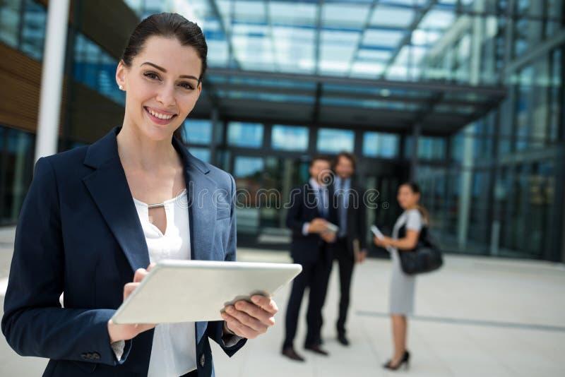 Stående av en affärskvinna som rymmer den digitala minnestavlan arkivfoton