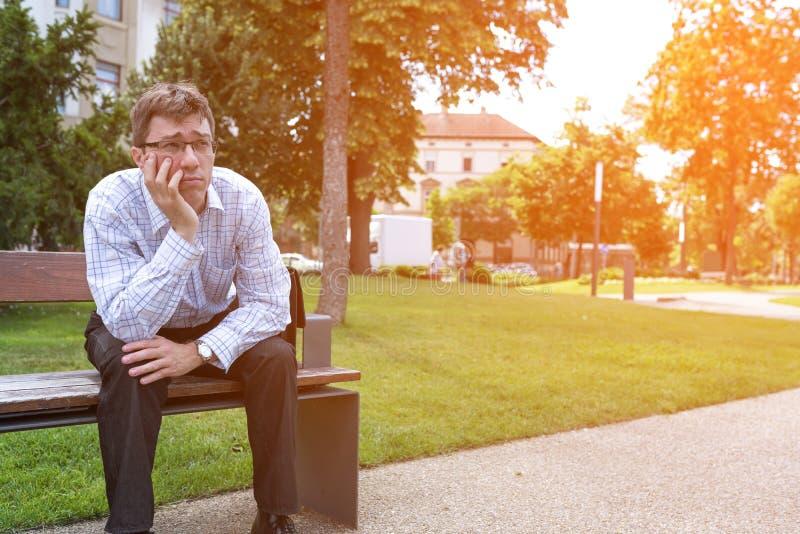 Stående av en affärsman som borras på en bänk fotografering för bildbyråer