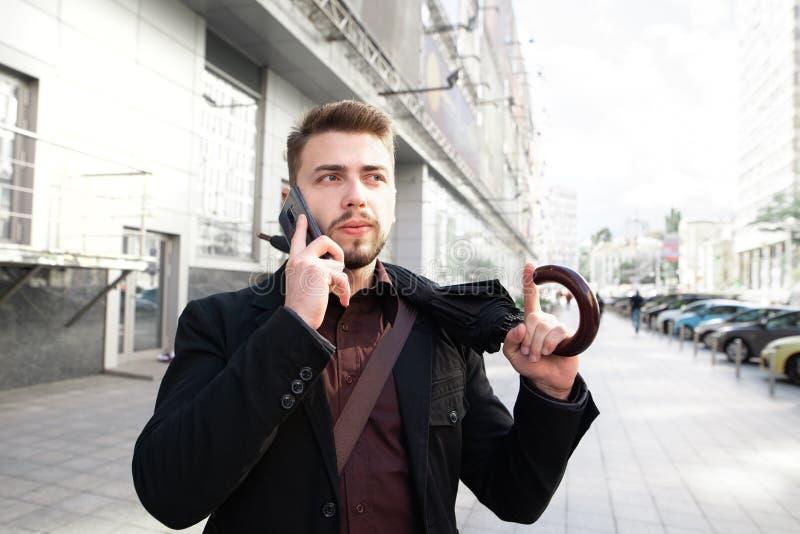 Stående av en affärsman som går runt om staden med ett paraply i hans hand och talar på telefonen arkivbild