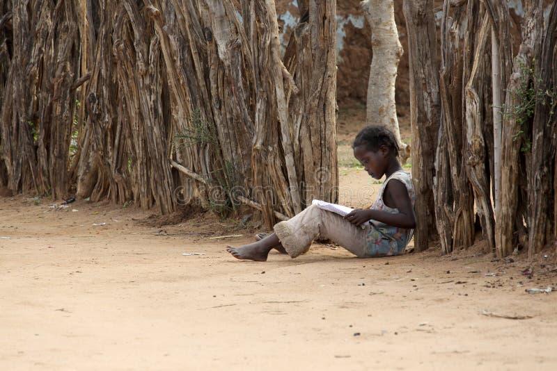 Stående av en afrikansk liten flicka som läser en bok fotografering för bildbyråer
