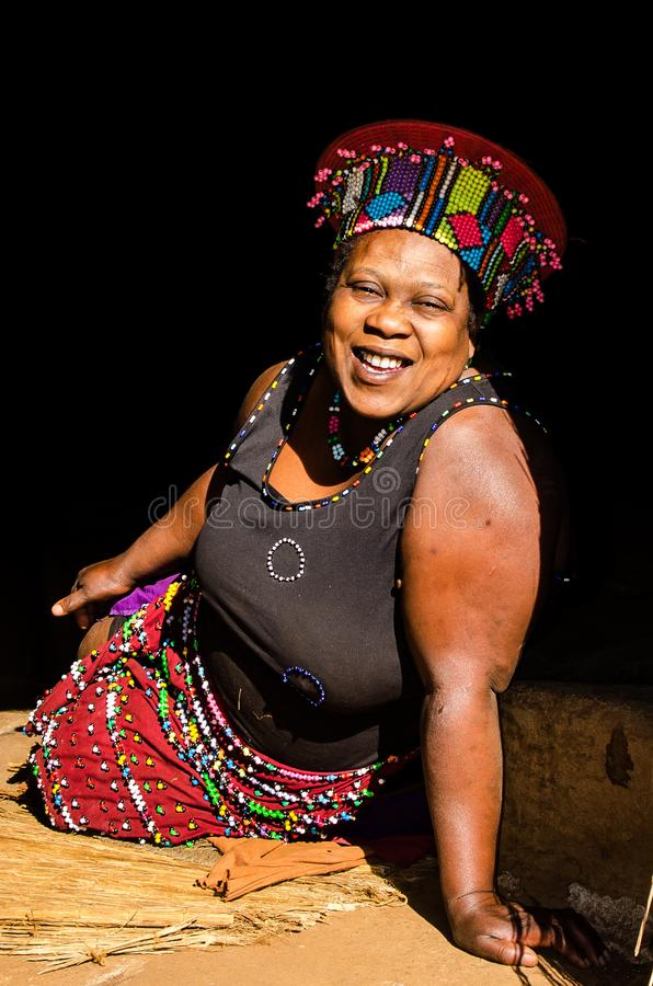 Stående av en afrikansk zulukvinna i den traditionella klänningen, hatt som ler livsstil Sydafrika royaltyfria foton