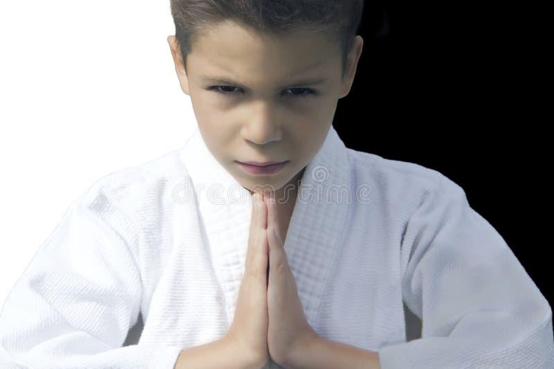Stående av en allvarlig pojke i en kimono som hälsar hans motståndare royaltyfri fotografi