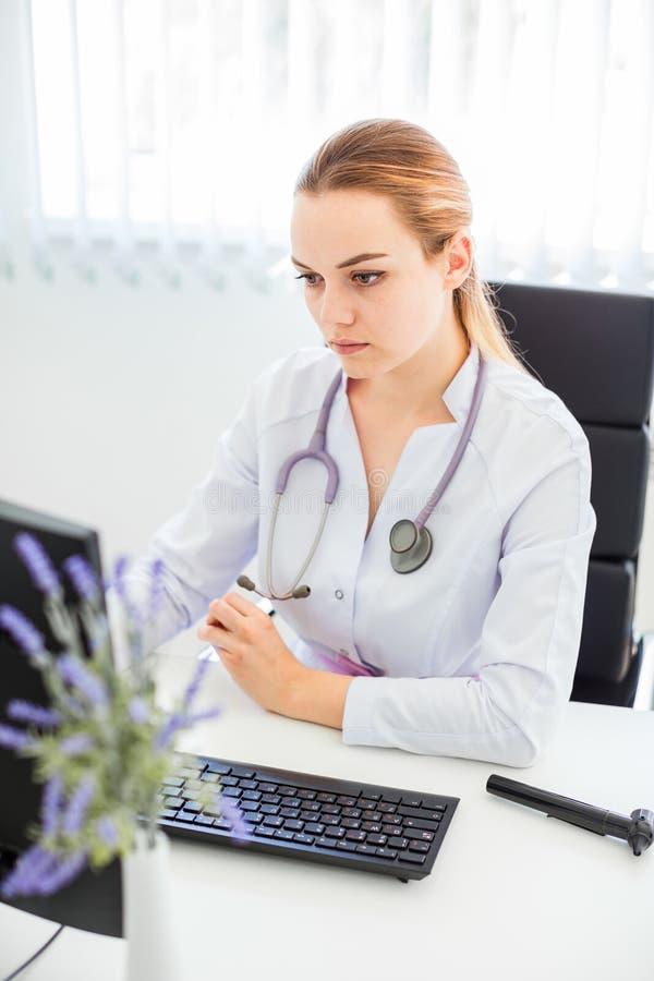 Stående av en allvarlig ung kvinnlig blond doktor som använder en dator i hennes kontor arkivbild