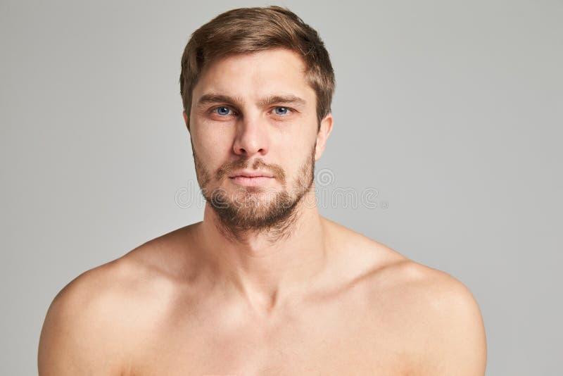 Stående av en allvarlig ung man med kala skuldror på en grå bakgrund, kraftiga simmareskuldror, skägg, karismatiskt som är vuxet, royaltyfri bild