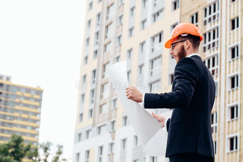 Stående av en arkitektbyggmästare som studerar orienteringsplanet av rummen royaltyfri bild