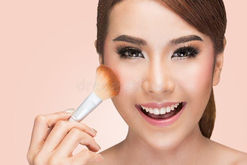 Stående av en asiatisk kvinna som applicerar det torra kosmetiska tonala fundamentet på framsidan genom att använda makeupborsten royaltyfria foton