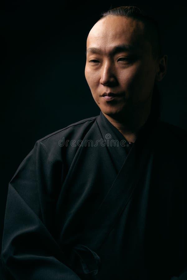 Stående av en asiatisk man i en svart ämbetsdräkt på en svart bakgrund arkivbild