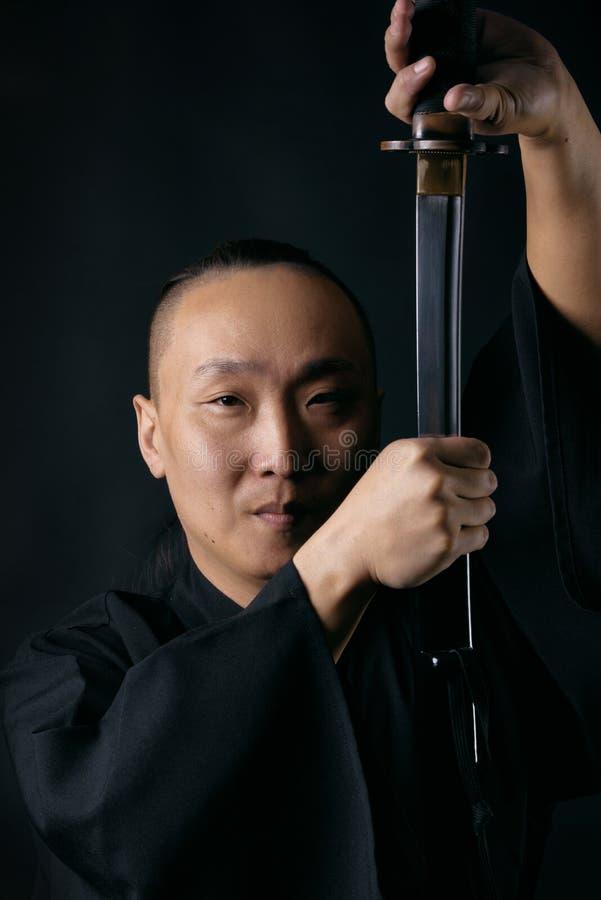 Stående av en asiatisk man med ett svärd i händer på en svart bakgrund, en samuraj royaltyfria bilder