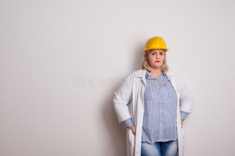 Stående av en attraktiv överviktig kvinna med det gula hjälm- och labblaget i en studio royaltyfri bild