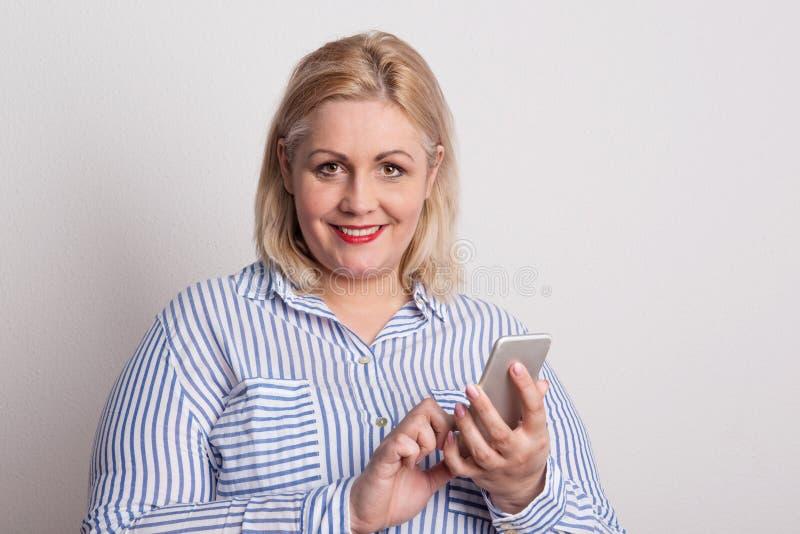 Stående av en attraktiv överviktig kvinna med smartphonen i en studio royaltyfri bild