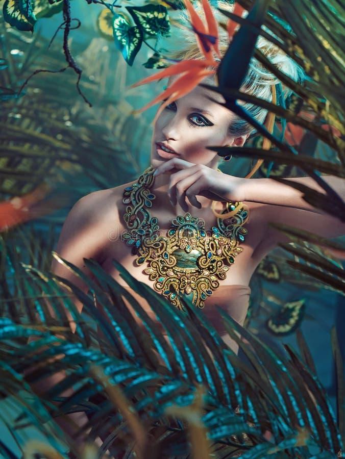 Stående av en attraktiv blond dam i djungeln arkivbild