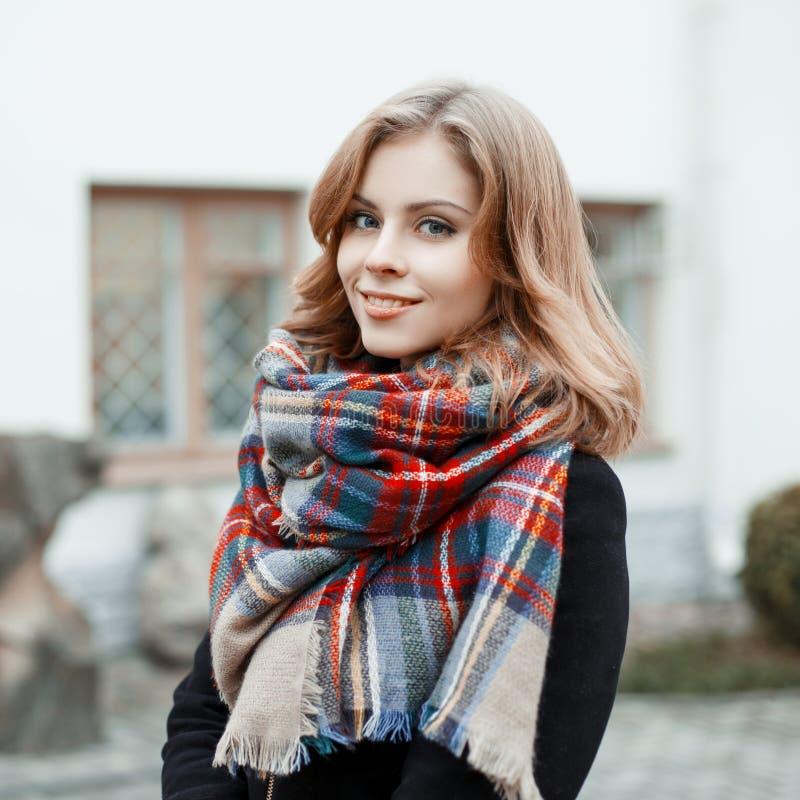 Stående av en attraktiv kvinna med blont hår med ett underbart leende i ett svart stilfullt lag med en woolen rutig varm halsduk arkivbilder