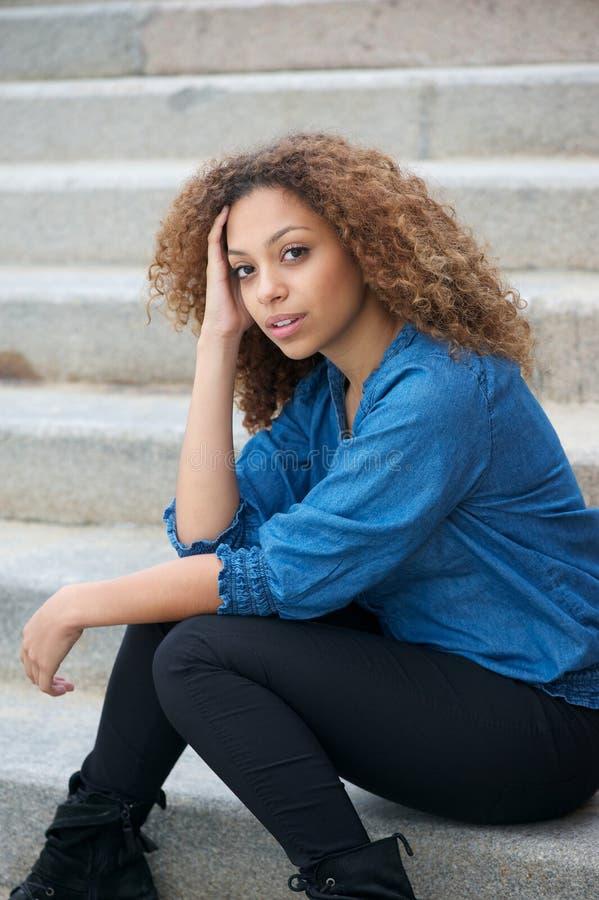 Stående av en attraktiv kvinna med sammanträde för lockigt hår utomhus royaltyfria bilder