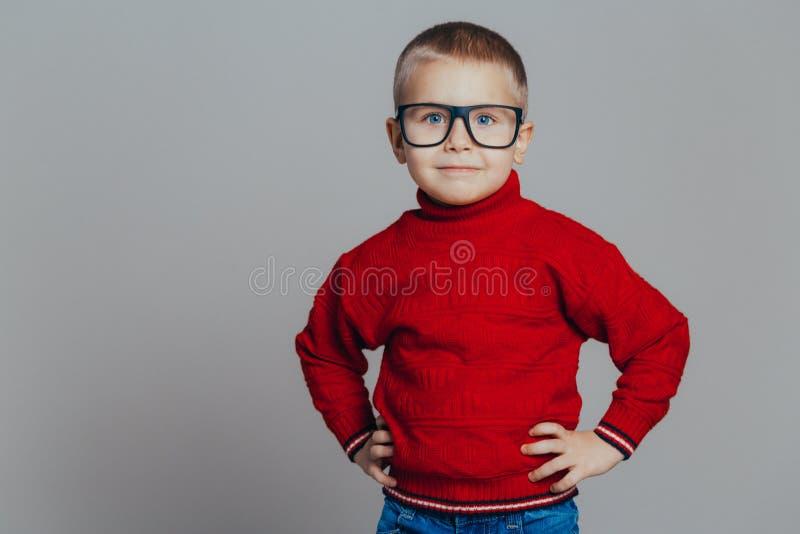 Stående av en attraktiv le pojke i en röd tröja och en svart exponeringsglasnärbild royaltyfria bilder