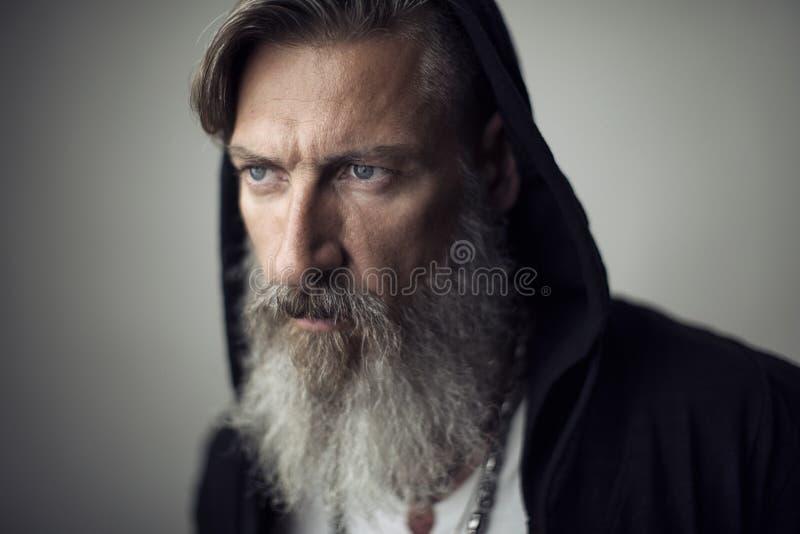 Stående av en attraktiv man med ett grått skägg och en huv arkivbild