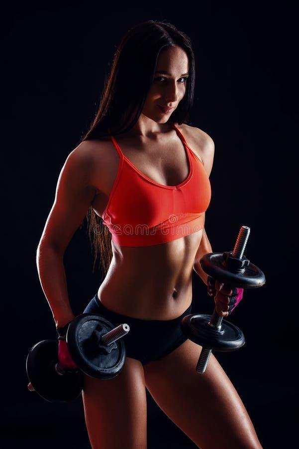Stående av en attraktiv ung konditionkvinna i sportswearen som gör genomkörare med hantlar på svart bakgrund arkivfoton