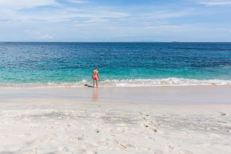 Stående av en attraktiv ung man på en tropisk strand royaltyfri bild