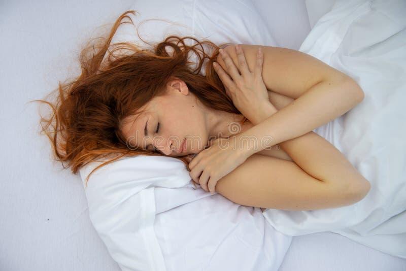 Stående av en attraktiv ung rödhårig kvinna som kopplar av i säng arkivbild