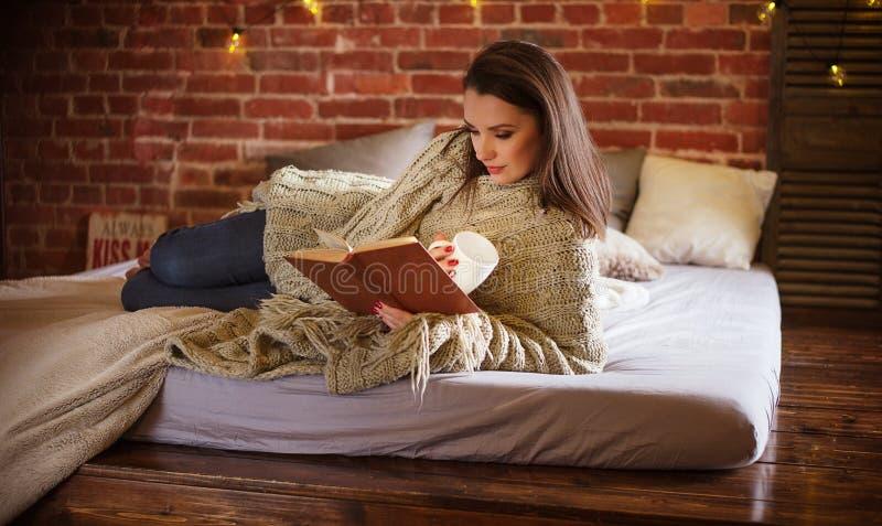 Stående av en avkopplad kvinna som läser en berättelse på den mjuka sängen royaltyfri bild