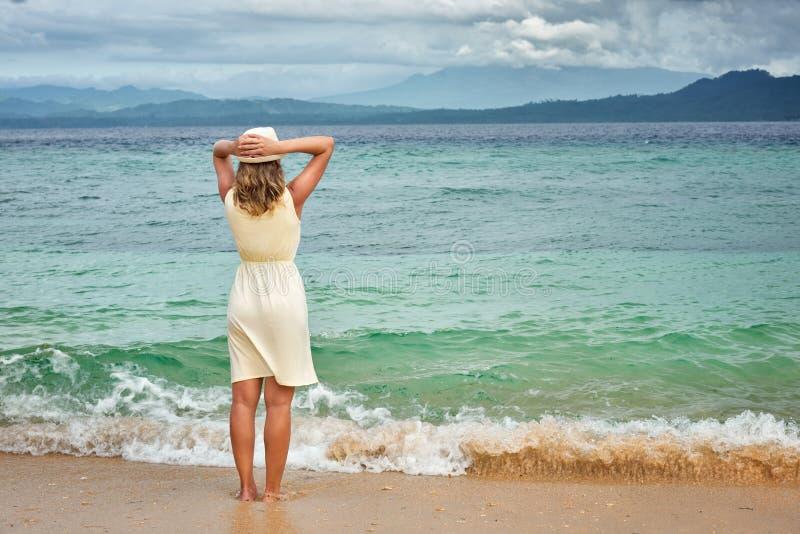 Stående av en bärande vit klänning för attraktiv womanl på en strand royaltyfri bild