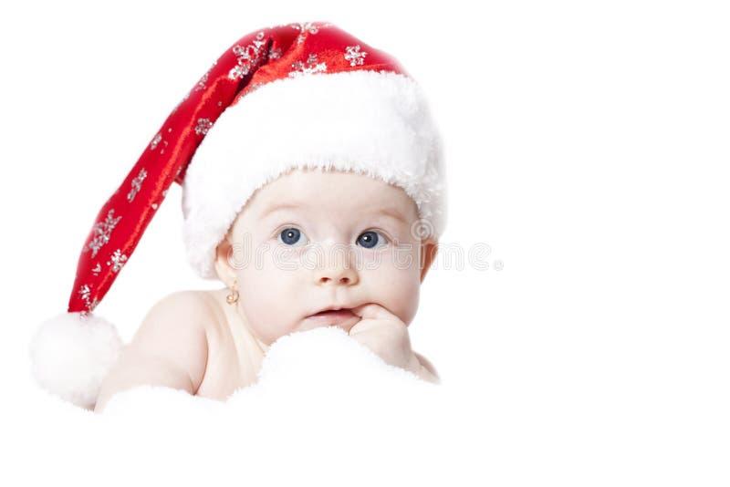Stående av en behandla som ett barn med jultomtenhatten som isoleras på vit arkivfoton