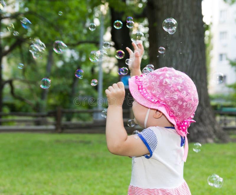 Stående av en behandla som ett barn och såpbubblor arkivfoto