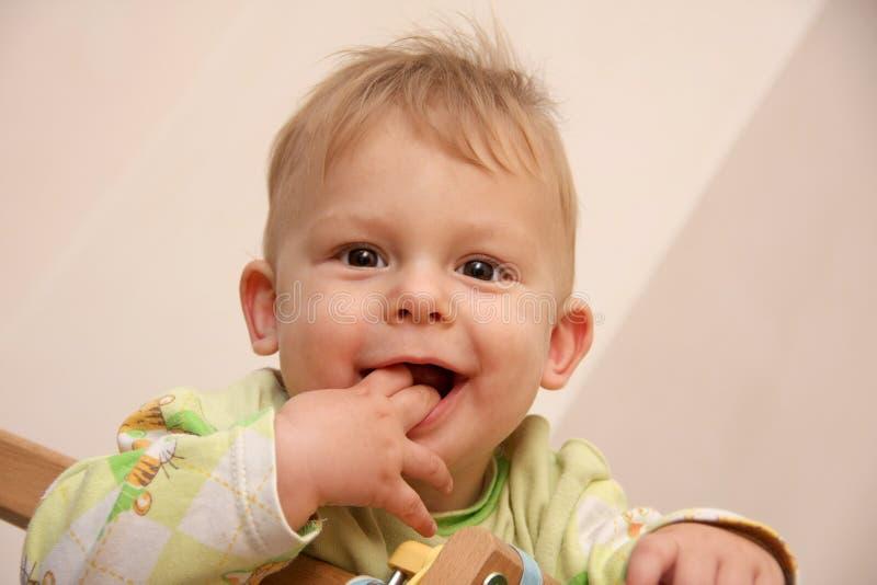 Stående av en behandla som ett barnpojke som rymmer hans två fingrar i hans mun royaltyfri foto