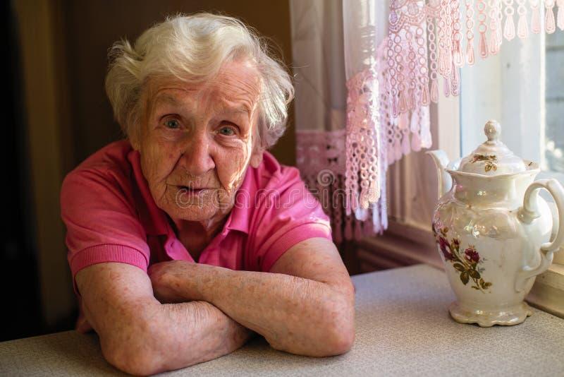 Stående av en bekymrad äldre kvinna i det hans huset fotografering för bildbyråer