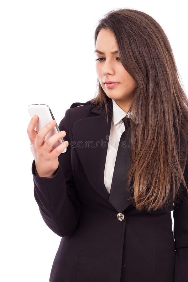 Stående av en bekymrad affärskvinna som ser hennes smarta telefon royaltyfria bilder