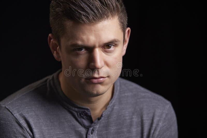 Stående av en bekymrad ung vit man som ser till kameran royaltyfria bilder