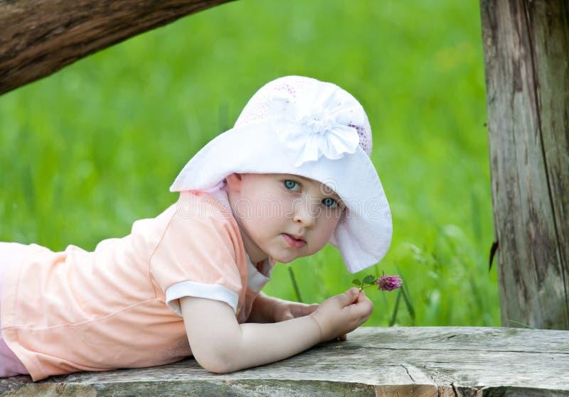 Stående av en blomma för liten flickaholdingsommar arkivbilder