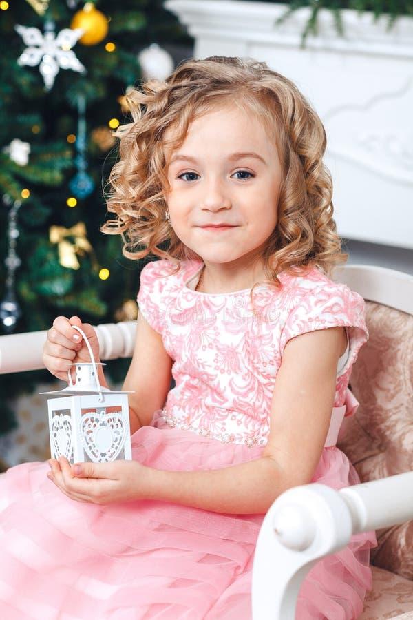Stående av en blond flicka i en rosa klänning mot bakgrunden av en julgran med en vit ljusstake i händerna arkivfoton