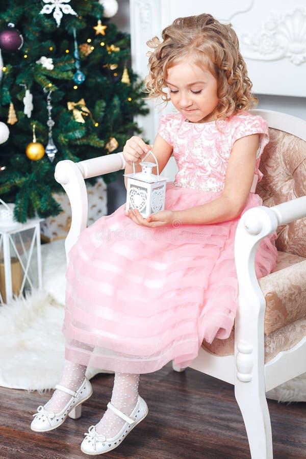 Stående av en blond flicka i en rosa klänning mot bakgrunden av en julgran med en vit ljusstake i händerna royaltyfria foton
