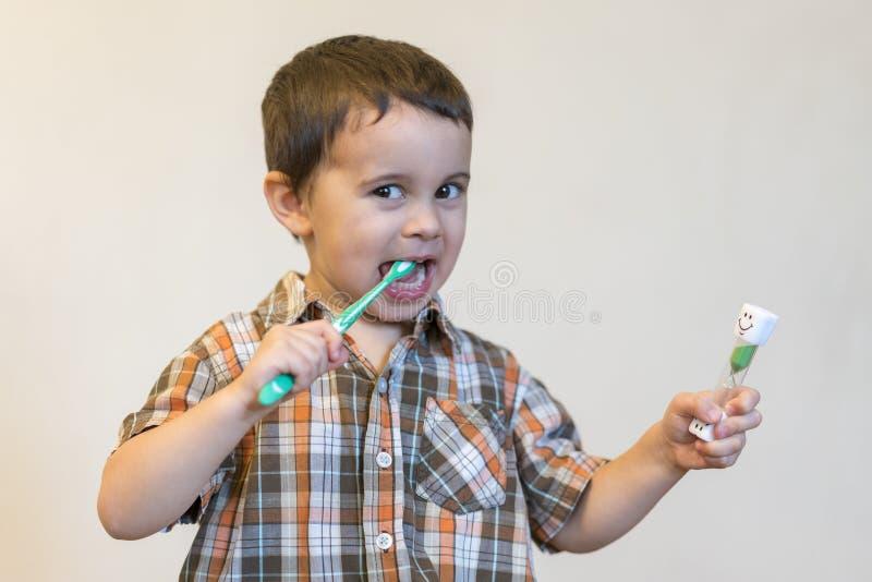 stående av en blond pojke för härlig gullig caucasian med en tandborste Pys som borstar tänder och ler, medan ta omsorg av arkivbild