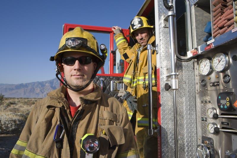 Stående av en brandman med coworkeren i bakgrunden fotografering för bildbyråer
