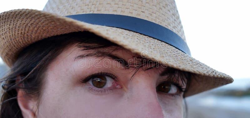 Stående av en brunögd brunett i en hatt som ser rak in i kameran med breda ögon, närbild arkivfoto