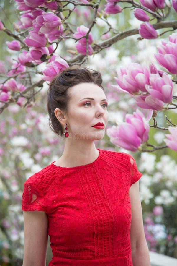 Stående av en brunett i en röd klänning i en trädgård av blommande magnolior arkivfoton