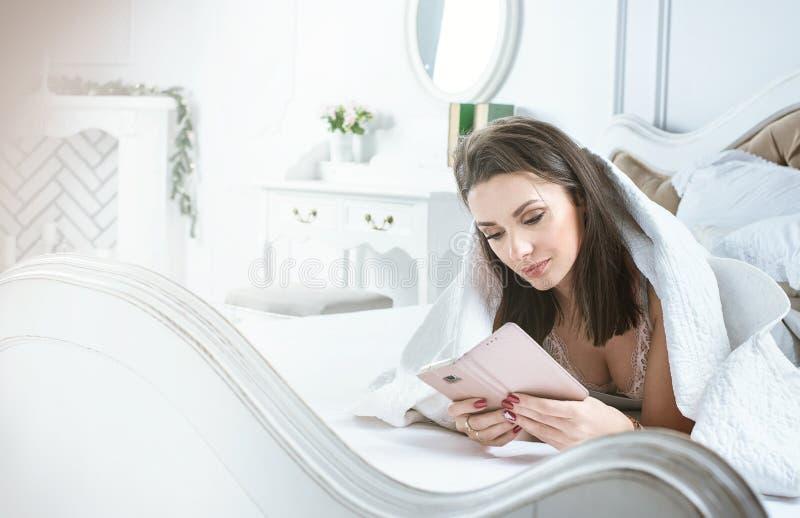 Stående av en brunettdam som använder en smartphone, medan ligga i säng royaltyfri bild