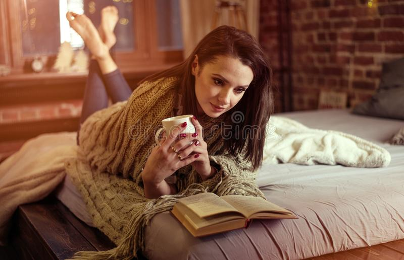 Stående av en brunettdam som läser en bok i en vinterafton royaltyfria foton