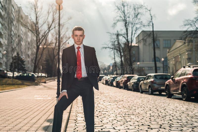 Stående av en brutal man i en svart dräkt och ett rött band En ung grabb sitter på gatan längs det gammalt stenar vägen royaltyfri fotografi